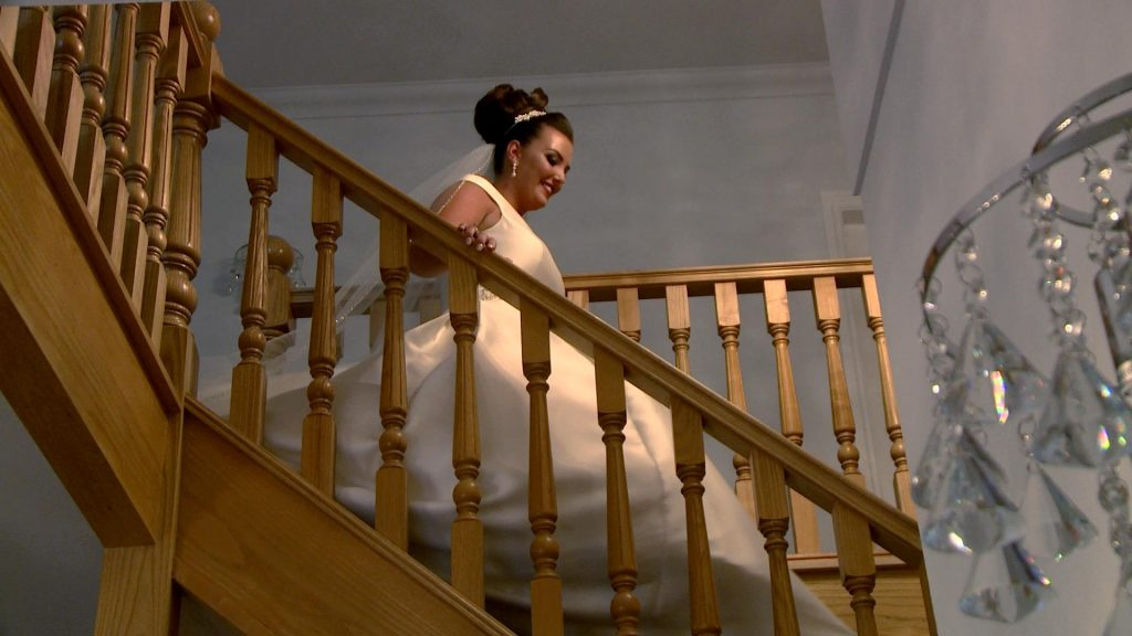 a bride glides down the stairs at her parents home in Prenton wearing an off the shoulder white ellis bridal dress and classic high bun and veil