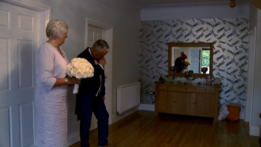 the dad fights happy tears as he sees his daughter for the first time in her wedding dress at their home in Prenton