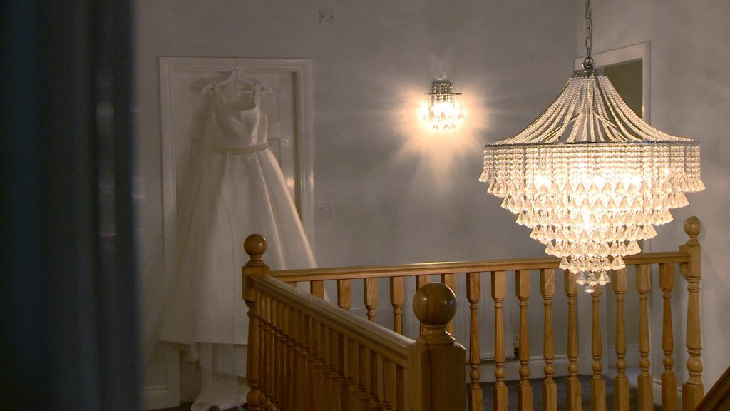 a stunning white satin Ellis bridal dress hangs on a door frame by an elegant chandelier by the staircase
