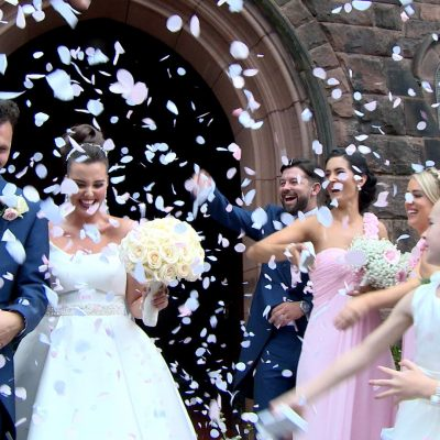 a bride and groom are showered in biodegradable pink and white confetti outside Saviours church in Oxton Wirral for their wedding video