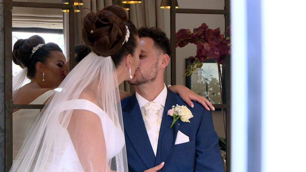 a bride and groom enjoy a relxed kiss between photos as the videographer catches a more natural moment from behind a door at Thornton hall