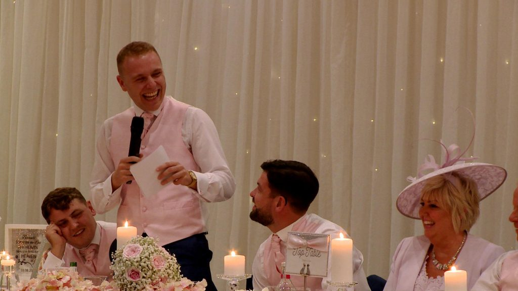 a best man laughs during his speech in front of a sparkly lit white backdrop during a wedding at Thornton Hall