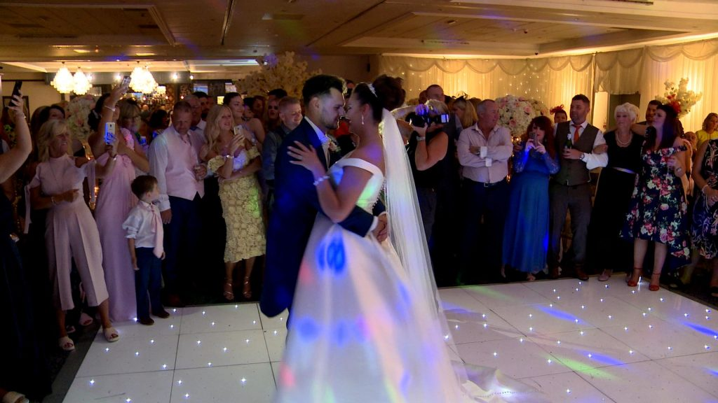 the bride and groom enjoy a slow and romantic dance on their sparkling white dancefloor in front of guests during their wedding reception at Thornton Hall hotel and spa in the wirral