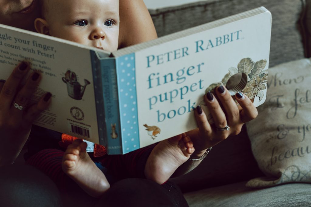 a little boy sits on his Mum's knee as they read a peter rabbit finger puppet book. You can see his eyes peering over the top and his little feet under the book. from a family photo shoot in Sale Manchester
