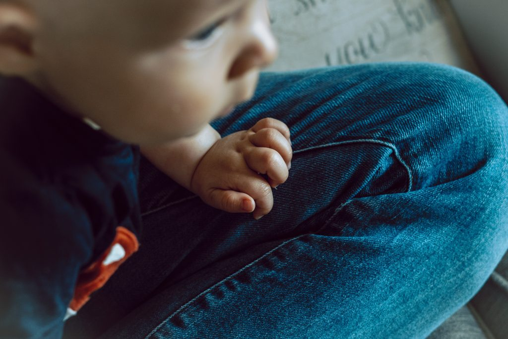 a close up of a little boys hand leaning on his Daddy's knee as they watch tv together at home in Manchester