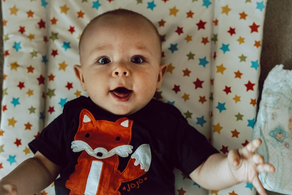 A blue eyed baby boy is wide eyed staring up at the family photographer with a navy fox t shirt on laying on his colourful star changing mat at home