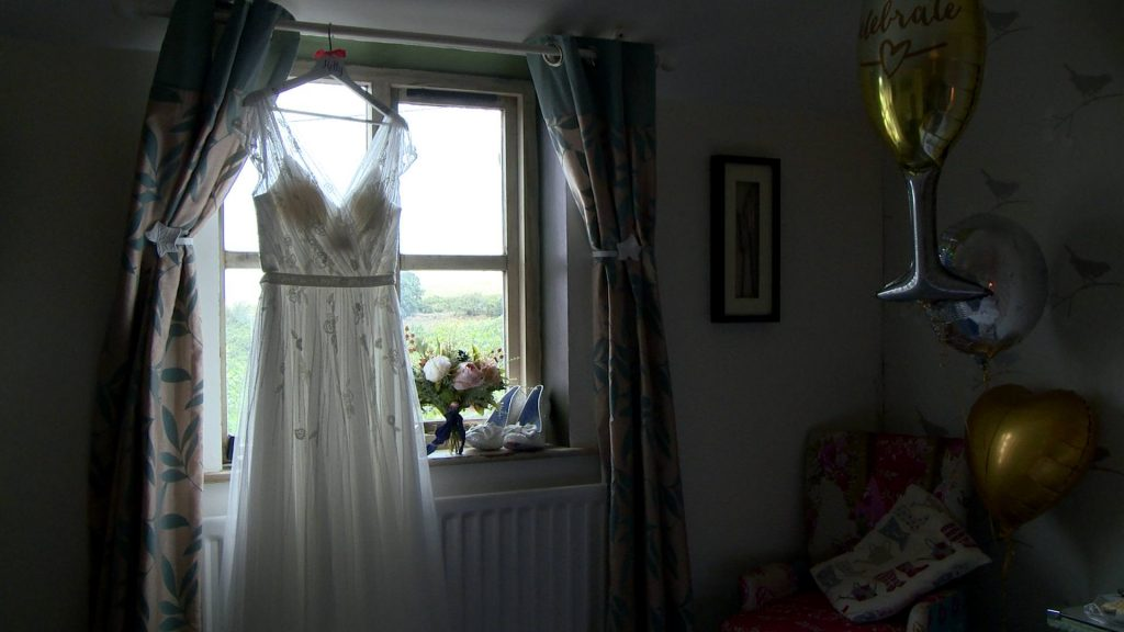 a vintage inspired wedding dress hangs on a wooden bridal hanger in front of a bright window at Abels Harp in Shrewsbury