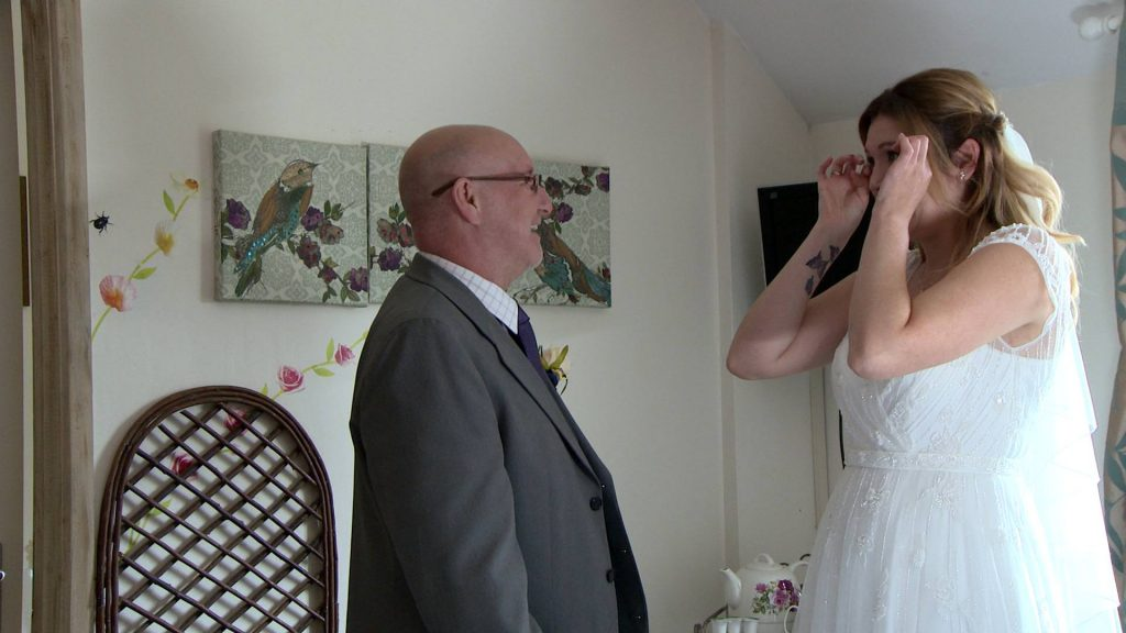 the bride wipes her tears away after her Dad sees her for the first time in her wedding dress captured for the wedding video