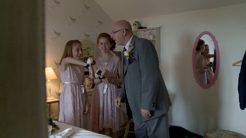 a wedding video still watching father of the bride, their grandad, seem impressed at the girls flower and minion corsages for his daughters wedding at Abels harp