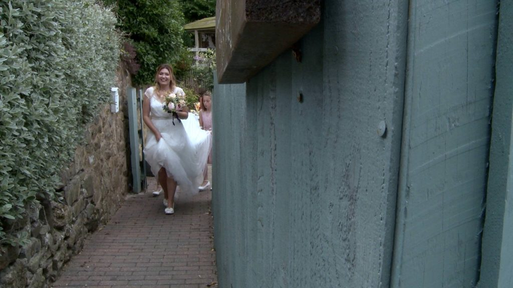 a bride walks beside a pretty green fence as her daughters carry her train at abels harp