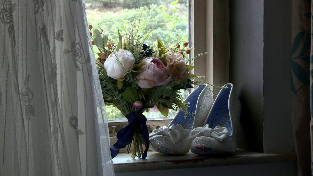 a pair of white glitter irregular choice bridal shoes sit on a window sill beside the brides dress and artificial peony bouquet