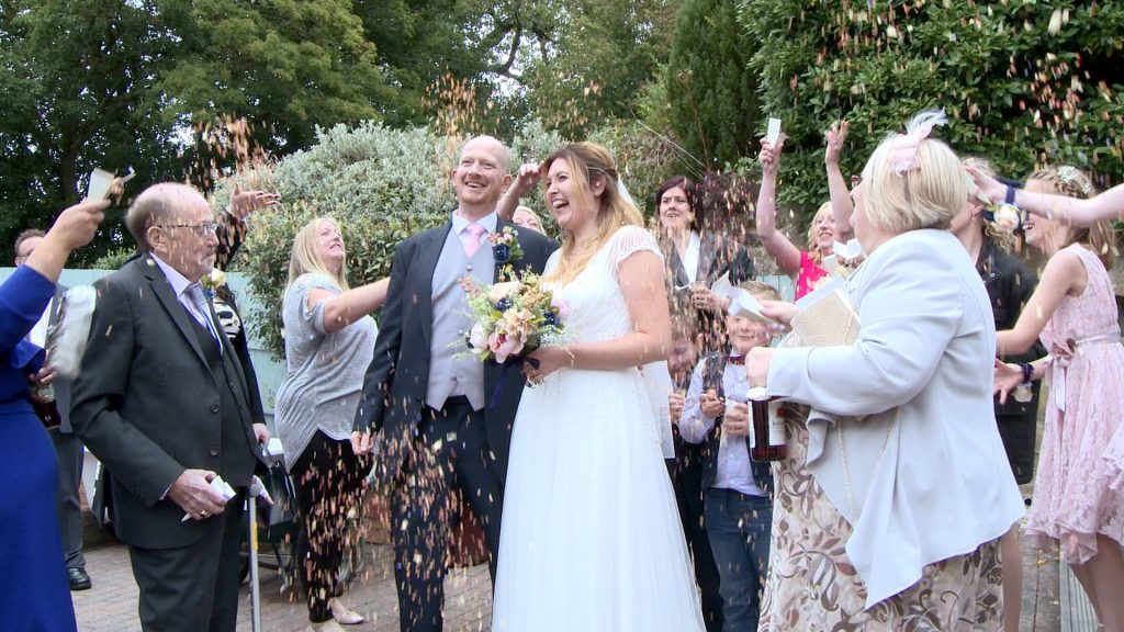 guests laugh and shout out as they shower the bride and groom in dried rose wedding confetti  for the wedding video at Abels Harp