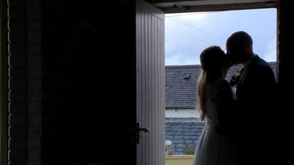 a bride and groom enjoy a kiss for the video stood in the doorway of Abel's Harp