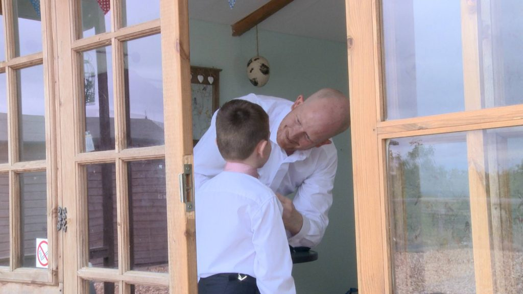 A dad helps fasten the buttons of his sons shirt before his wedding at abels harp the videographer is standing outside the pod as they get dressed inside