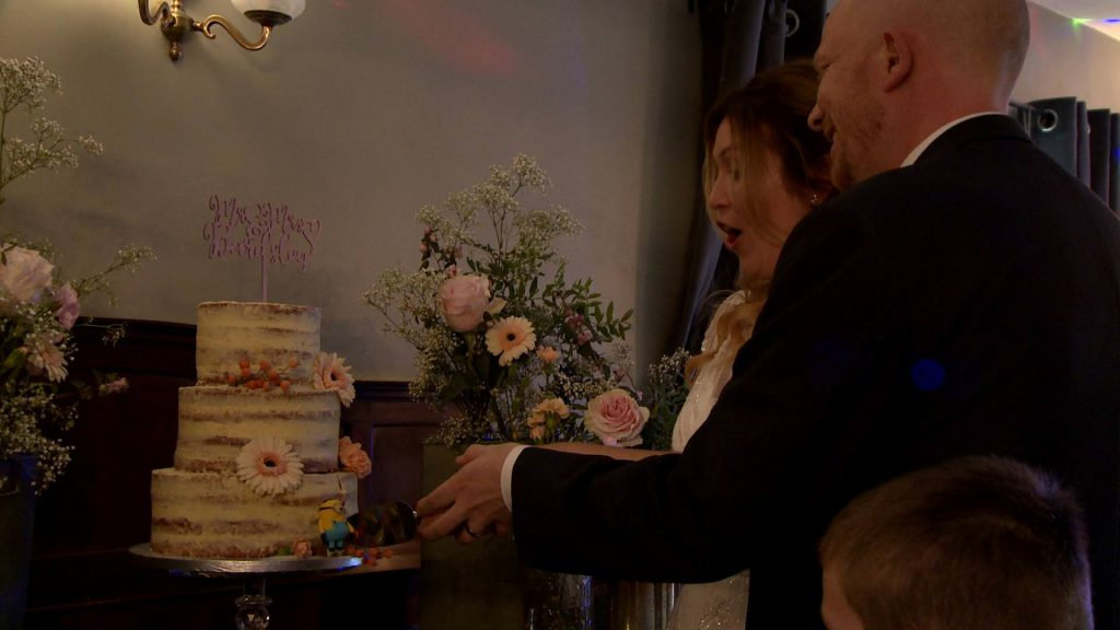 the bride and groom nearly knock the naked cake over as they cut it and the knife gets stuck near one of their Minions