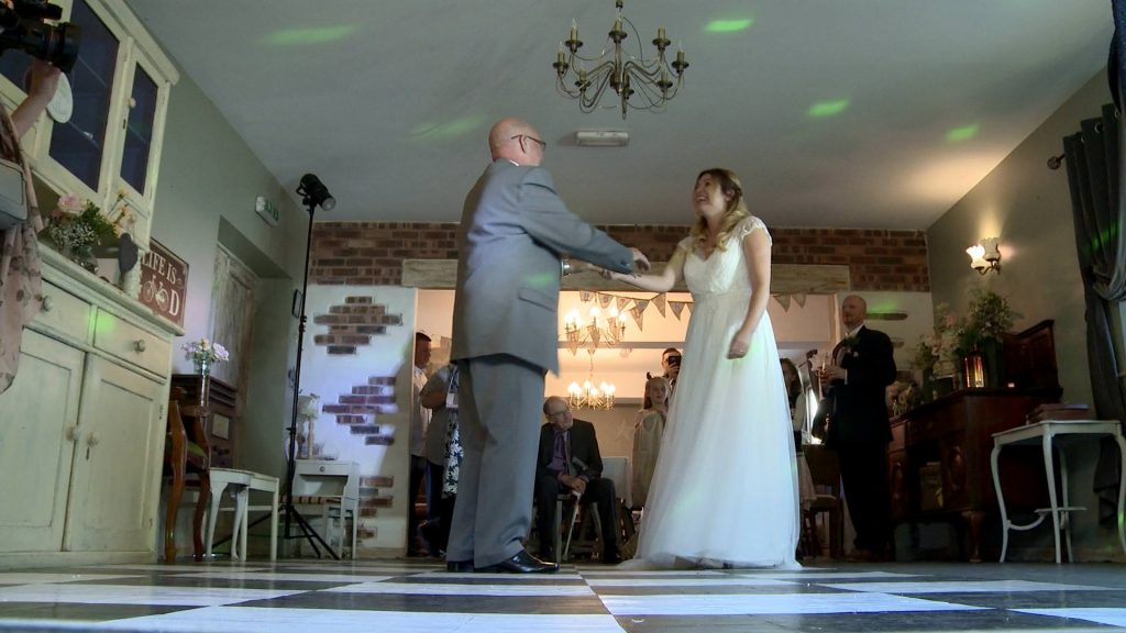 a bride enjoys a dance with her dad on a traditional black and white dancefloor at Abel's Harp