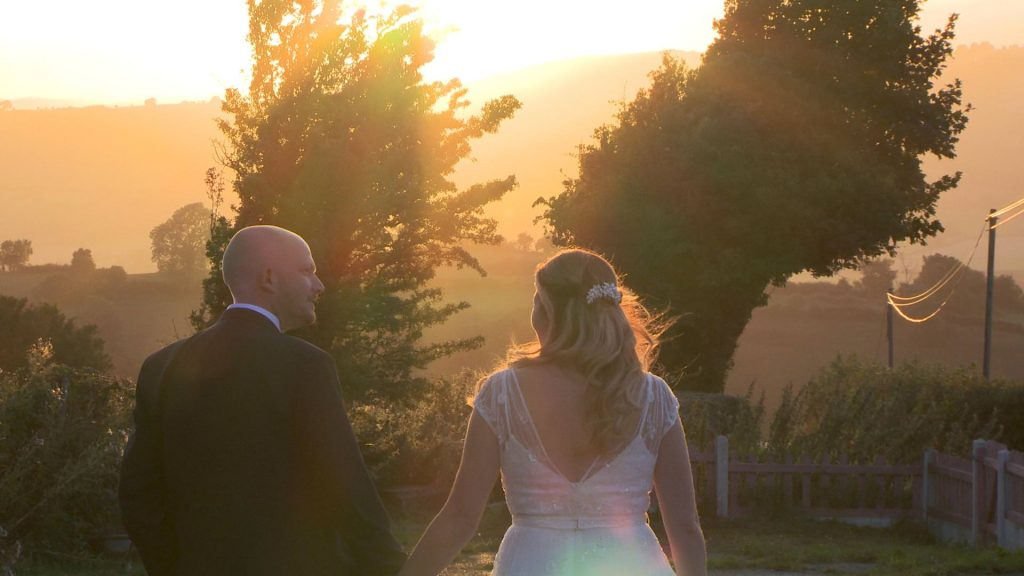 a bride and groom walk and smile with a golden hour liht surrounding them during their wedding evening outside Abel's Harp
