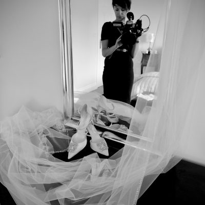 a black and white photo of charlene from love gets sweeter wedding videos filming a pair of white bridal shoes and veil with wedding photographer Jane Hockey