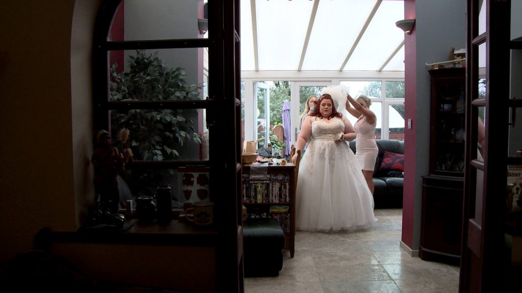 A bride stands in the conservatory of her parents house having the finishing touches added to her wedding day look with her veil being held up by the hairdresser