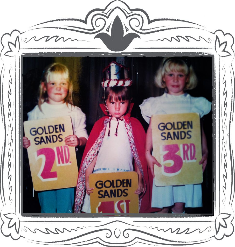 a young girl pouts and sulks wearing a crown and red cape after winning the golden sands model competition at Butlins in skegness