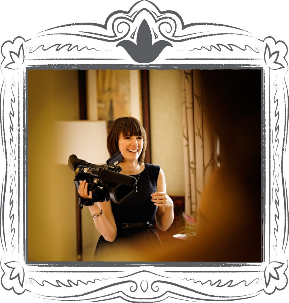 a female videographer laughs and holds her sony video camera whilst filming a bride getting ready at her wedding venue in Cheshire. Photo taken by Mick Cookson at Mottram Hall