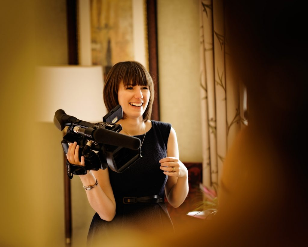 Charlene from Love Gets Sweeter a female wedding videographer laughing whilst holding a Sony video camera in a bridal suite at Mottram Hall in Cheshire