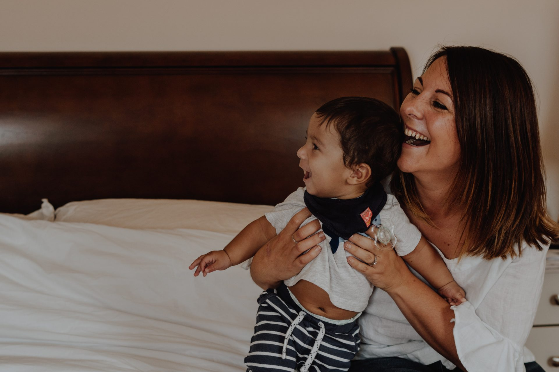 Mum laughs out loud whilst holding baby boy max sat on their large kingsize bed at home during a family photography and video shoot in Sale Manchester