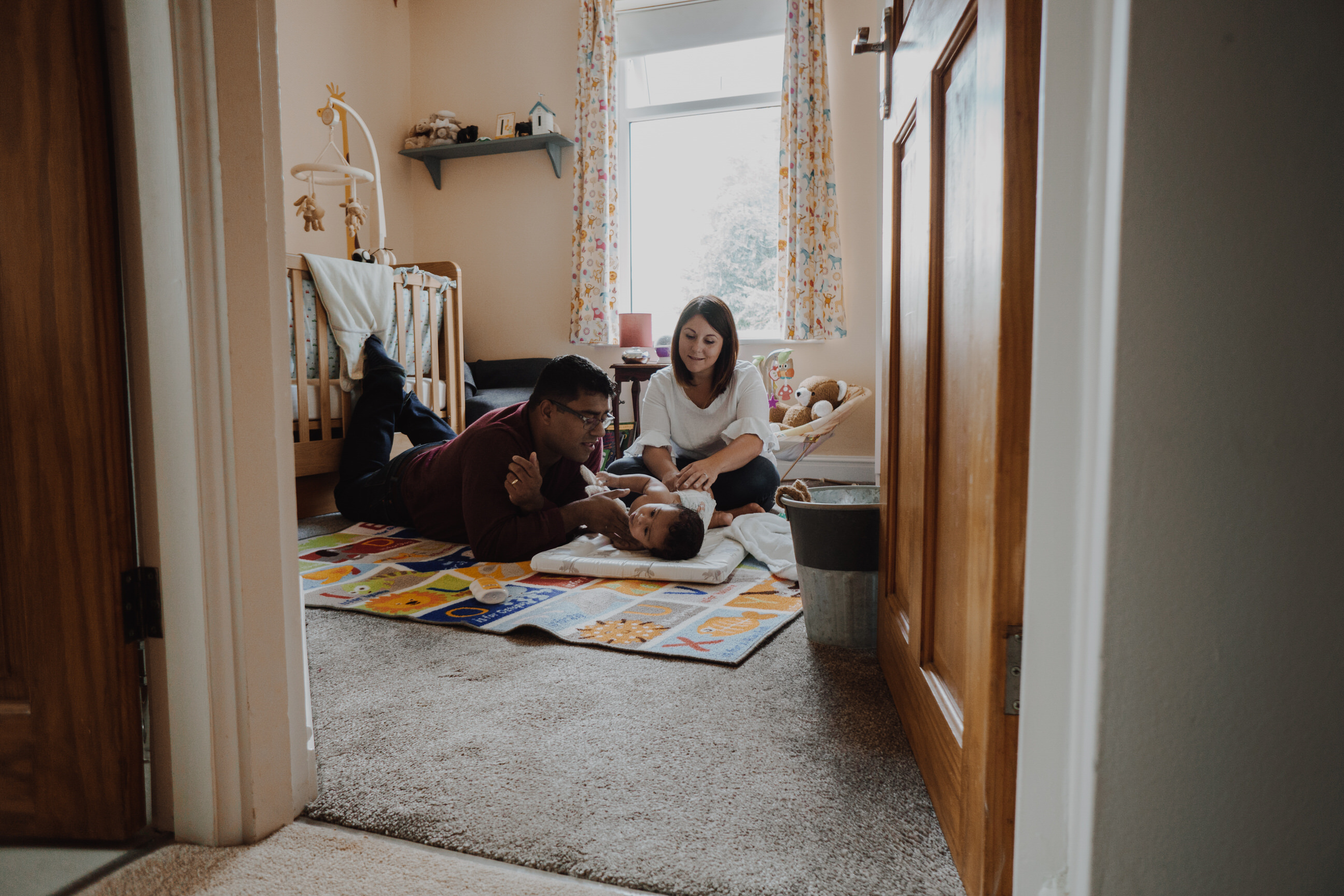 A mum and dad sit on the cream nursery bedroom floor during a nappy change at their home in Didsbury. The photo is taken through the bedroom door during their relaxed home family photography shoot near Manchester