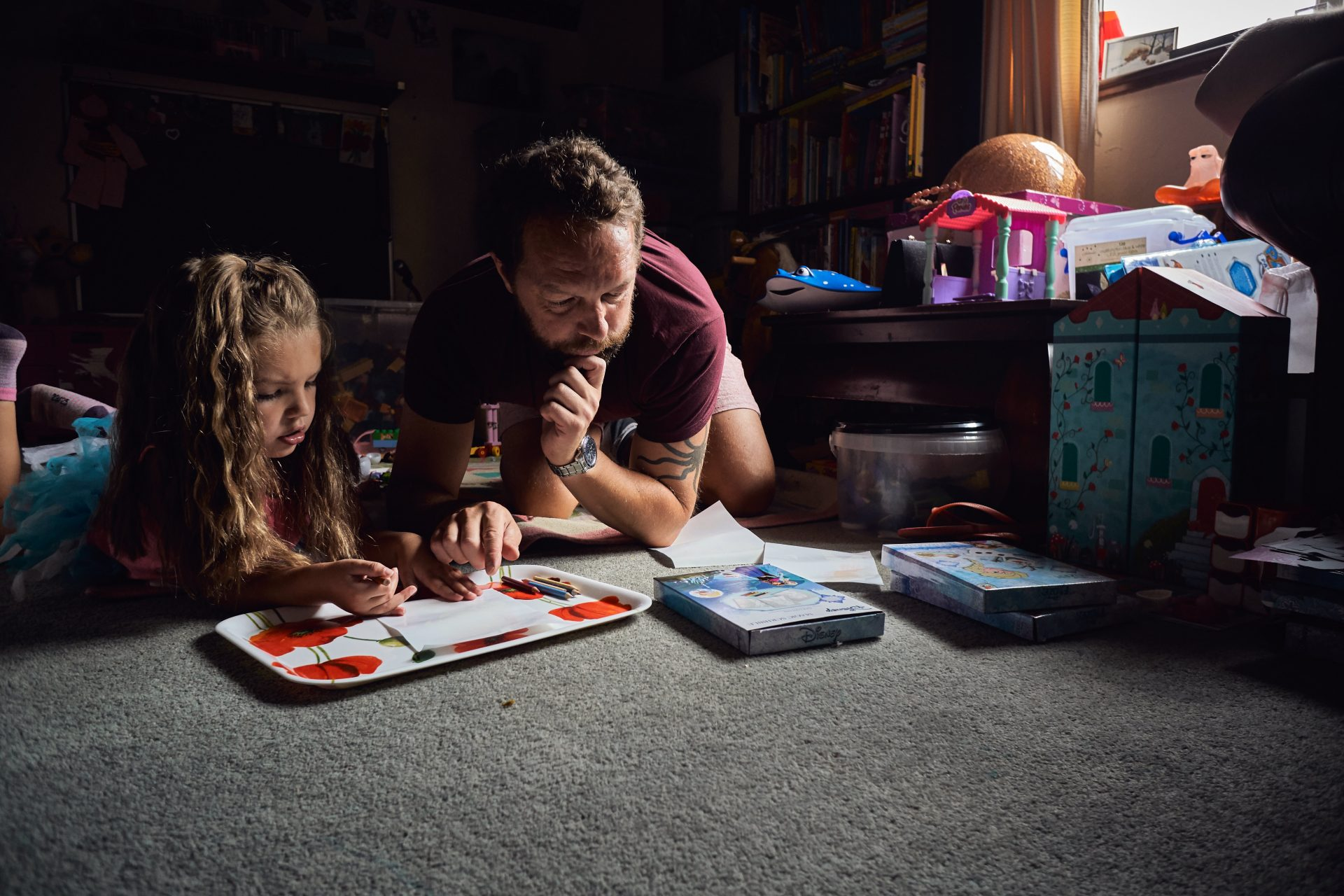 A dad leans on his chin looking puzzled as he works out a new craft book with his daughter in their play room during a relaxed family photography shoot in Lancashire