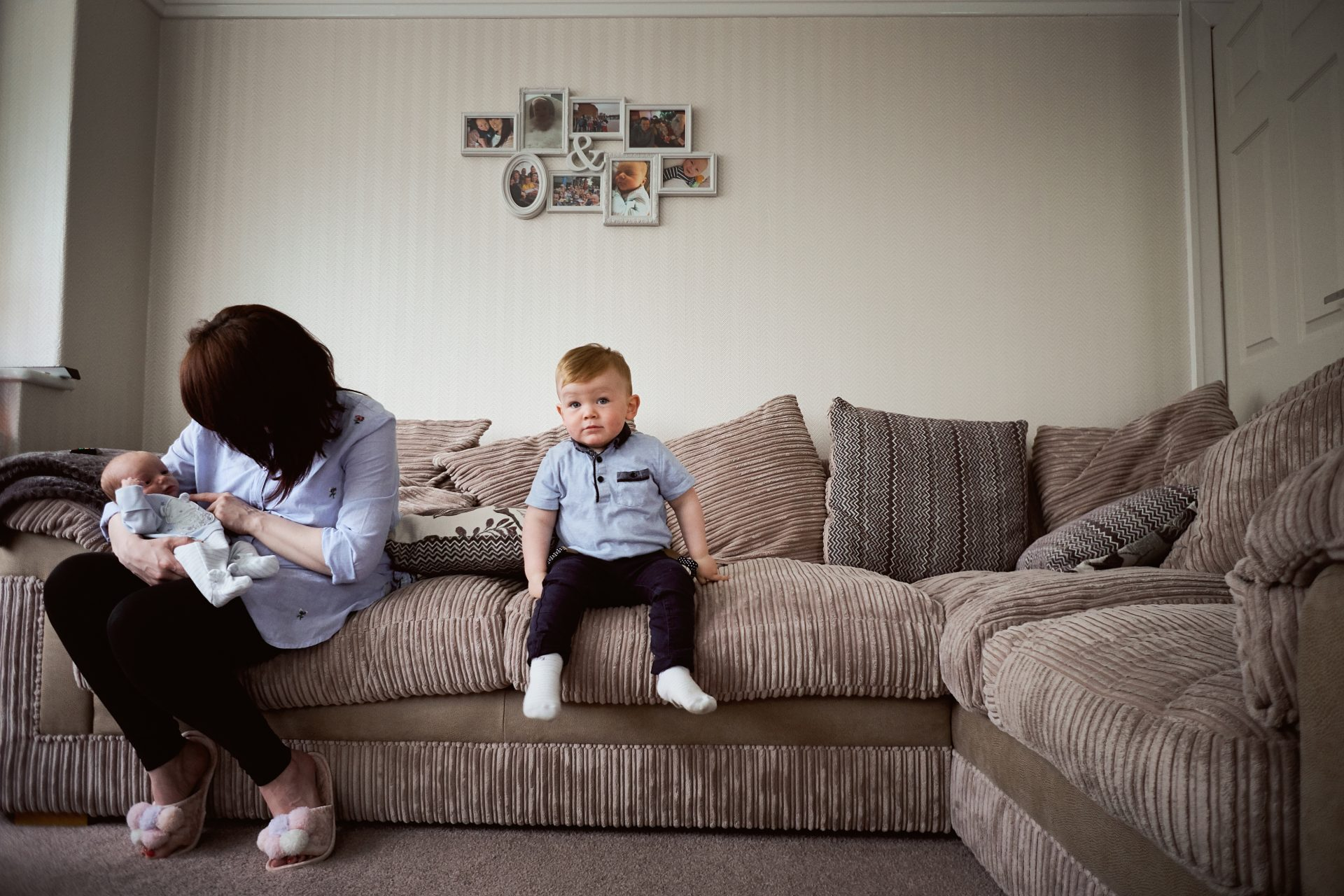 a relaxed family photograph from love gets sweeter of a mum sat on the sofa with one of the newborn twins and her toddler sat alone staring at the camera in the wirral