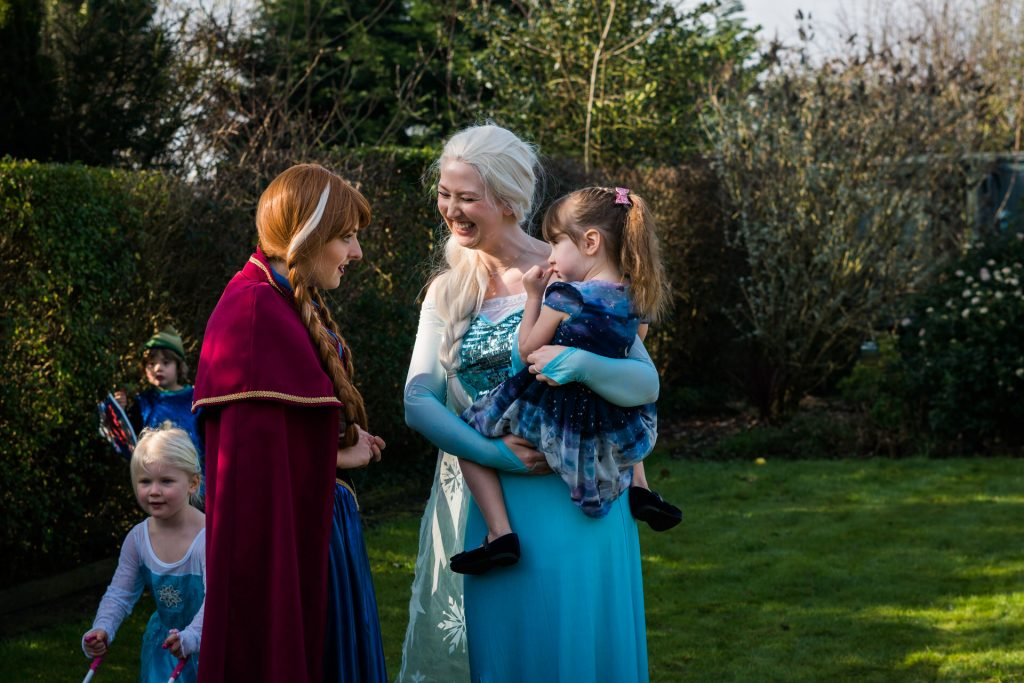 a photograph of a birthday party. elsa holds the birthday girl as they chat with Anna from Frozen during her 4th birthday party celebrations at home in Burscough