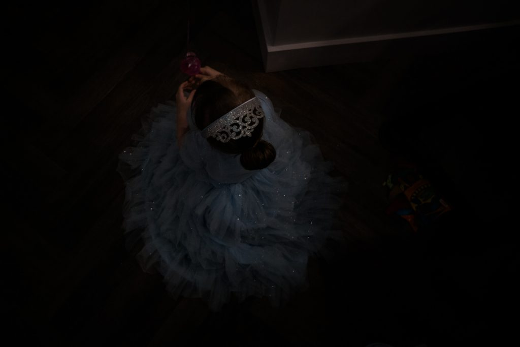 a family photograph from above of a 4 year old little girl sat on the floor in her cinderella princess dress and silver crown with her hair tied in a bun in the fat italian near Burscough