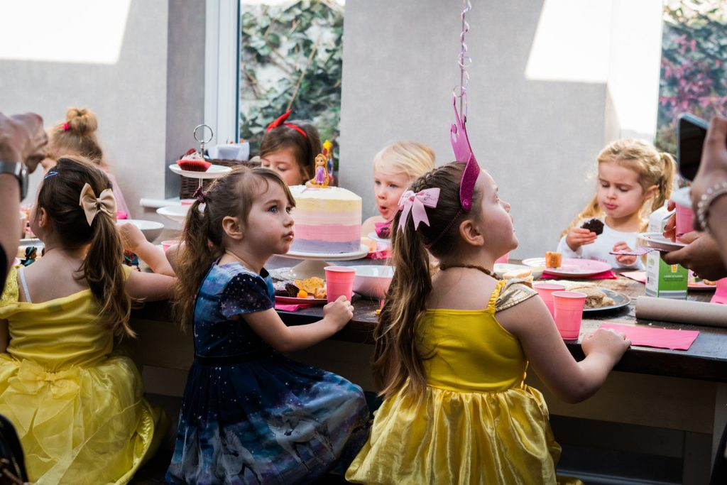 a group of young girls sit around a large dining table in a family home in Burscough eating their party food and waiting to cut the birthday cake. They're all wearing disney princess dresses for the party in Lancashire