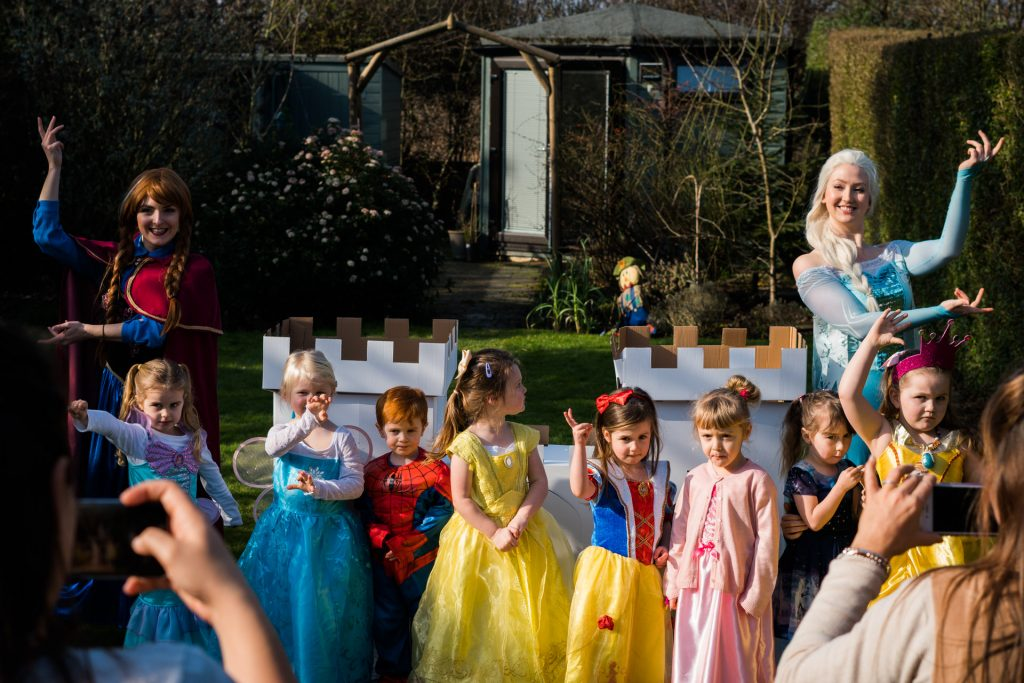 a group of 4 year olds dressed as disney princesses line up to pose in front of a cardboard castle in a family garden alongside Elsa and Anna from enchanted encounters in the north west. A natural documentary style professional photograph by Love Gets Sweeter in Burscough