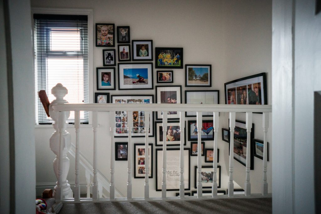 you can see the start of a fun family photo wall creeping up the stairs using black chunky photo frames on a white wall in a family home in Lancashire
