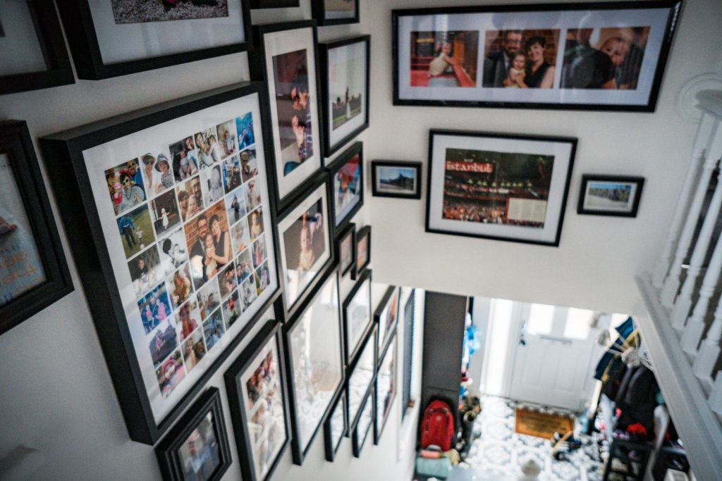 looking down the stairs to the front door we can see a colelction of chunky black picture frames with a variety of personal and professional family photographs framed in a feature photo wall at a home in Lancashire