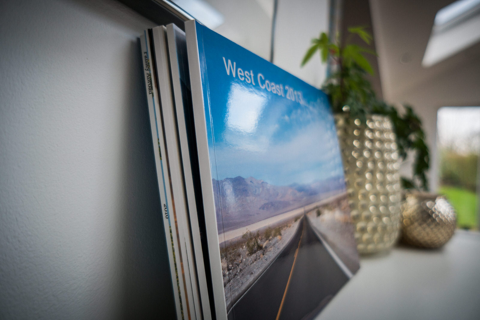 a close up photograph of a family holiday blurb photo book sat on an ikea shelf inside a family home in Lancashire