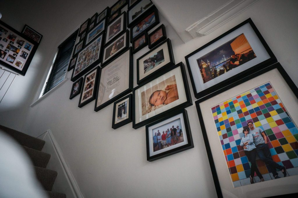 family photo wall inspiration. looking up the stairs there are lots of framed family photos using a black and white colour scheme giving it a modern feel for framing family photographs in Lancashire