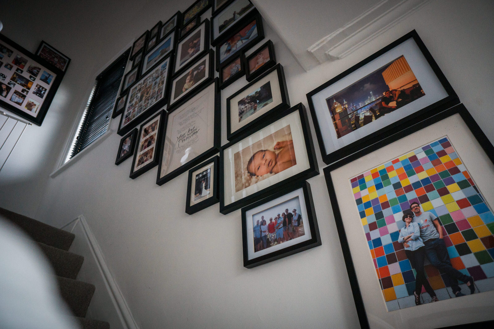 a photograph from the bottom of the stairs showing off a full black framed gallery wall in a family home in Lancashire