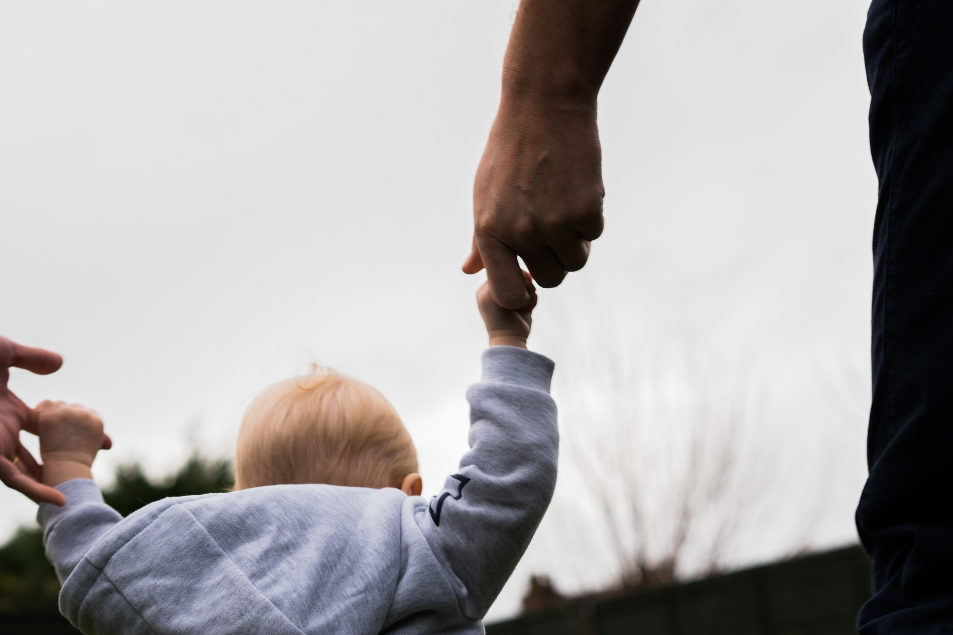 a close up of a girl holding her Dads hand during a outdoor family photoshoot near manchester