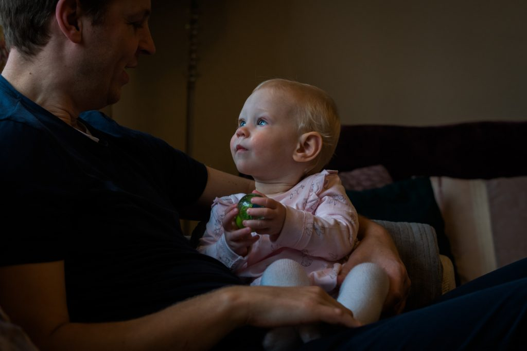 a little girl gazes up towards her dad with her big blue eyes whilst holding a ball. Captured by Love Gets Sweeter family photography and videography in lancashire