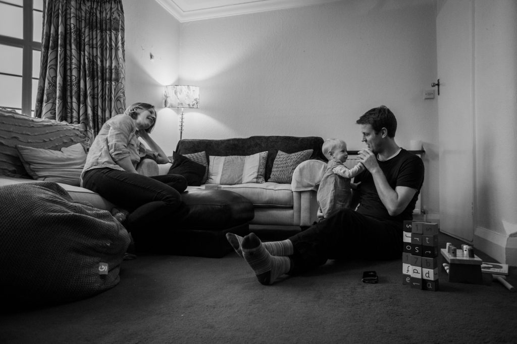 a black and white documentary style relaxed family photo in the living room as they play together during a family shoot in Hale