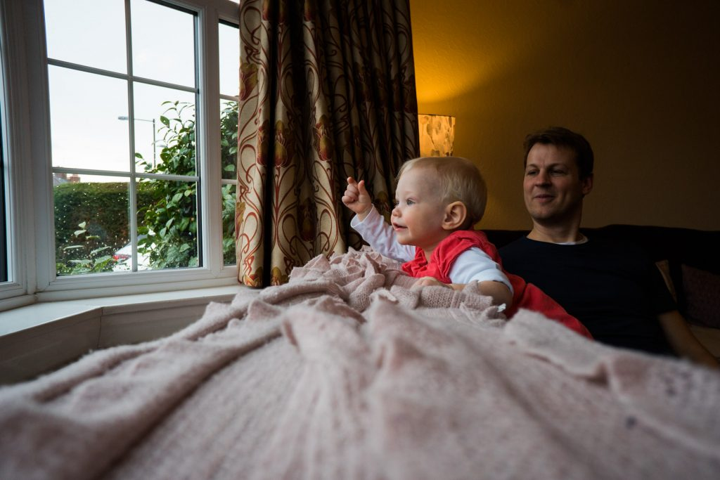 a little girl leans on the sofa and points at the rain outside the window during a family photo shoot at their home in hale