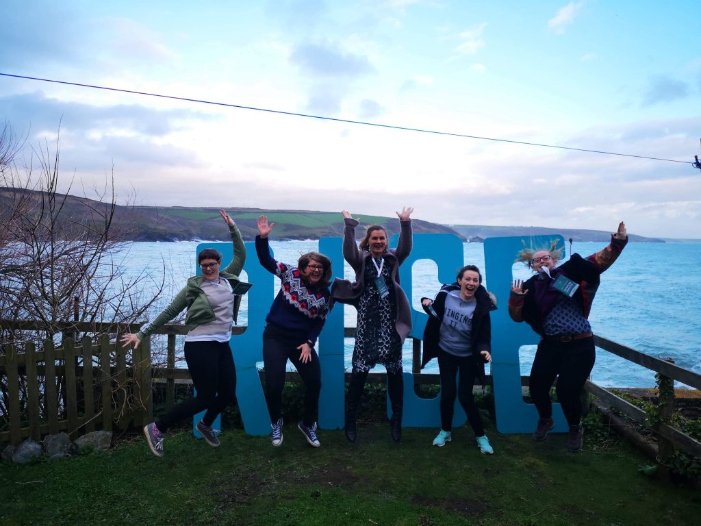5 female wedding videographers jump in the air for a photograph in front of giant blue letters spelling RISE at a cove in Cornwall for the RISE wedding filmmakers retreat