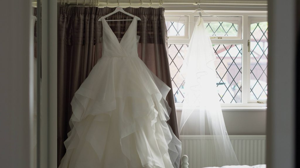 a white princess style tulle layered wedding dress hangs on a curtain rail next to the brides veil ready for the bride getting married in the wrral