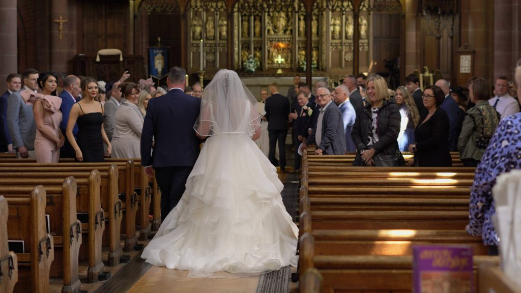 A wedding video still of a bride walking down the aisle in a princess style wedding dress at Oxton St Saviours in the wirral