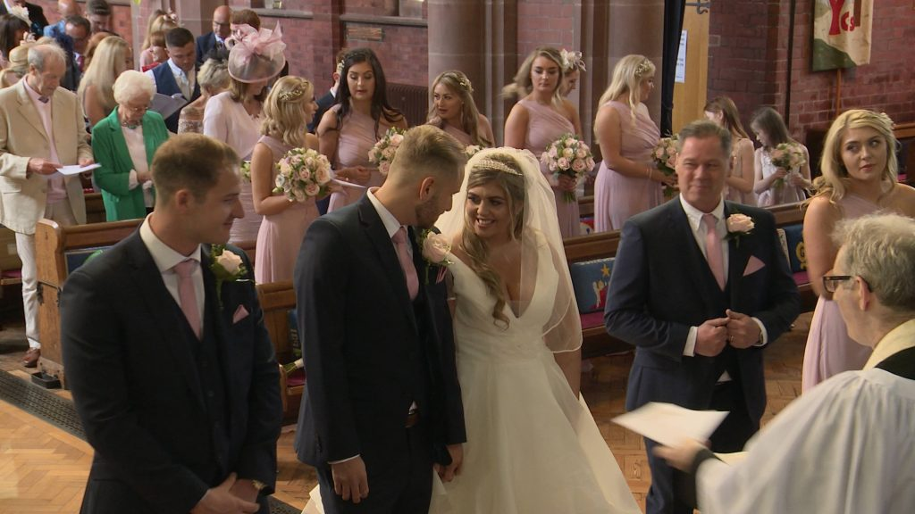 a wirral wedding videographer filmed the bride and grooms first look and smile at their wedding at Oxton St Saviours in Wirral