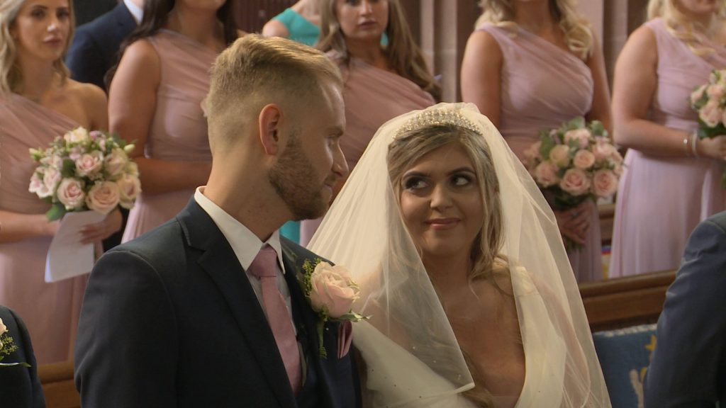a video still of the bride and groom glancing at each other with a little smile as they get married at Oxton St Saviours church in the wirral