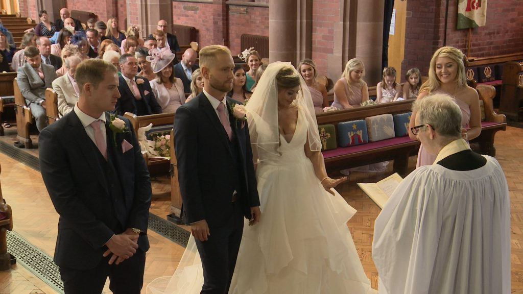 a wide shot from the wedding videographer as the bride looks down at her new wedding ring as she holds hands with her new husband at a church wedding in the wirral