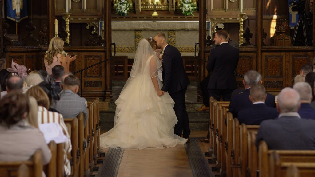 a wide shot from the wedding video at the top of the aisle as the bride and groom have their first kiss at oxton st saviours church